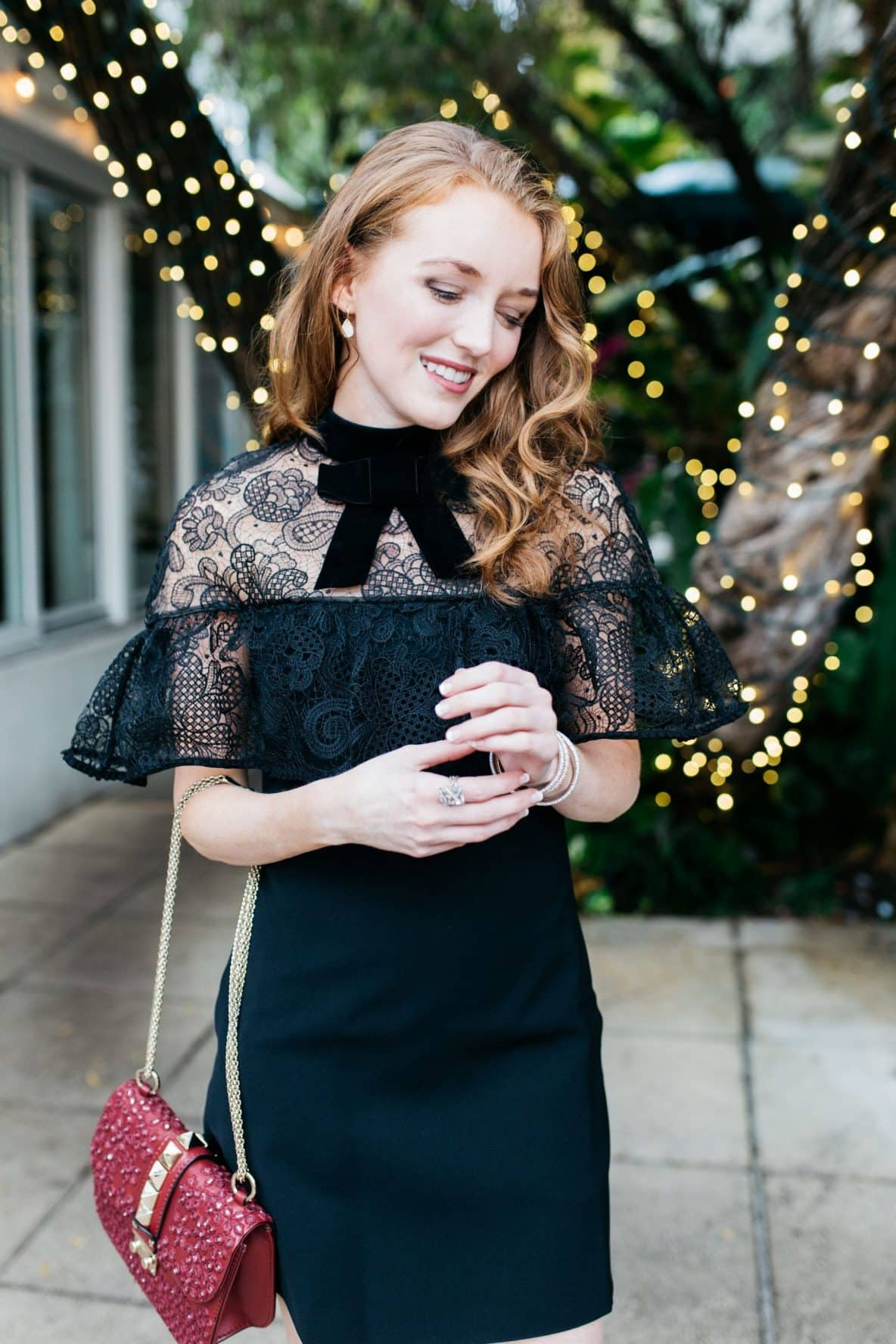 Holiday outfit, black self portrait lace overlay dress with Henri Bendel red studded handbag