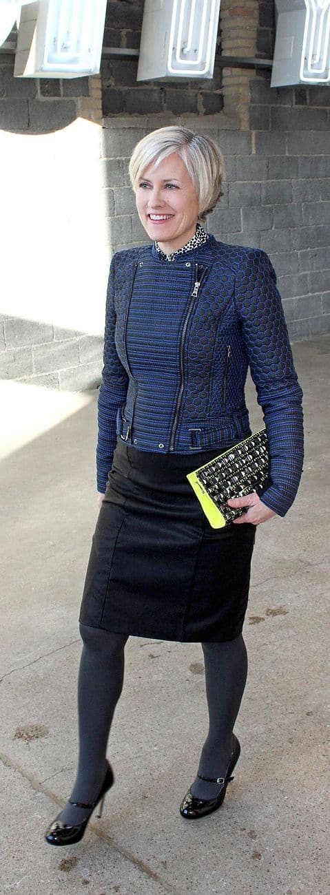 50 and stylish modern looks wearing leather, blue leather texture bomber jacket with black leather skirt