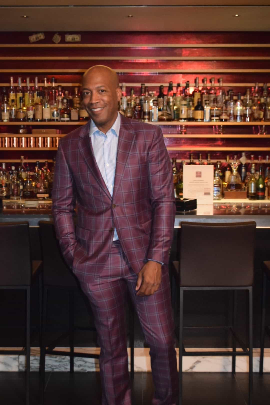 Barnette Holston wearing plaid wine color suit and striped button down