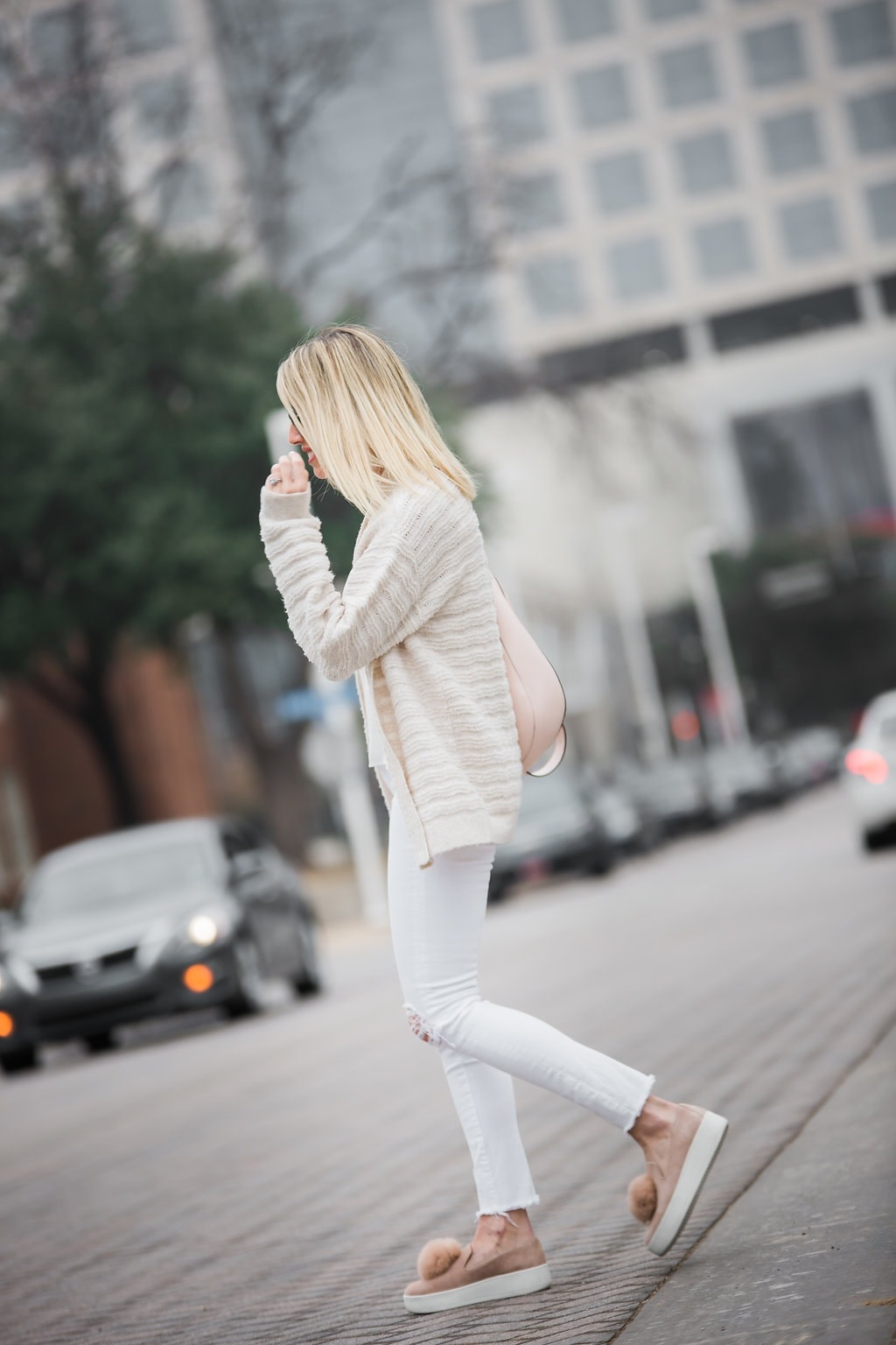 transition to spring women's outfit, white distressed jeans, beige cardigan and suede sneakers with pink bag